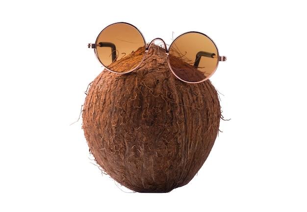Noce di cocco con occhiali da sole, concept art di estate e vacanze, cocco isolato su sfondo bianco