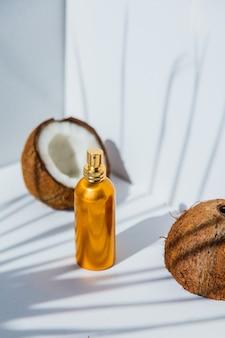 Noci di cocco e bottiglia di profumo su bacgkround bianco con le ombre