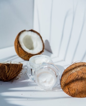 Noci di cocco e crema per la cura della pelle su bacgkround bianco con le ombre