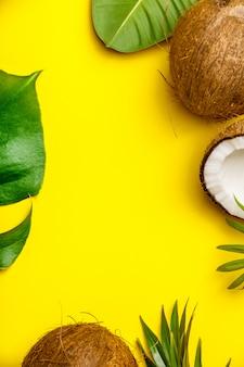 Noci di cocco e foglie tropicali su sfondo giallo,