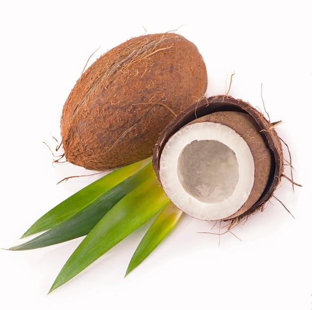 Noci di cocco con foglie su uno sfondo bianco.