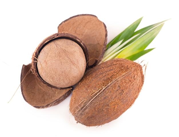 Noci di cocco con foglie su un bianco isolato.