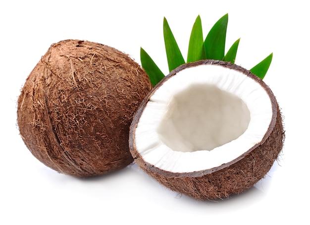 Noci di cocco con foglie su bianco