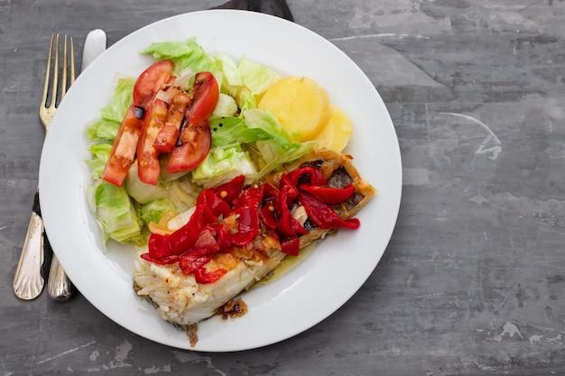 Merluzzo con peperone rosso, patate e insalata sul piatto bianco su fondo in ceramica