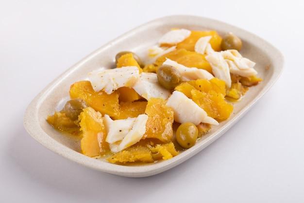 Baccalà con patate dolci e olive sul piatto su sfondo di carta grigia