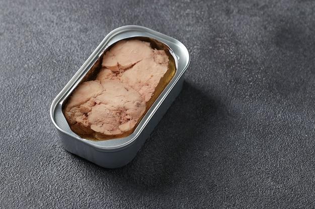 Fegato di merluzzo in un barattolo di ferro su sfondo grigio scuro con posto per il testo. formato orizzontale