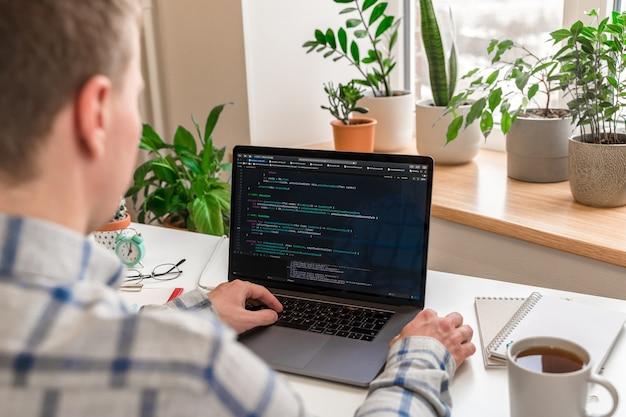 Codifica sullo schermo le mani dell'uomo codifica e programmazione sullo sviluppatore web di sviluppo di laptop sullo schermo