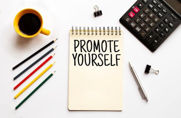 Tazza da caffè calculatornotepadpen e matite sullo sfondo bianco il concetto di business testo promuovi te stesso