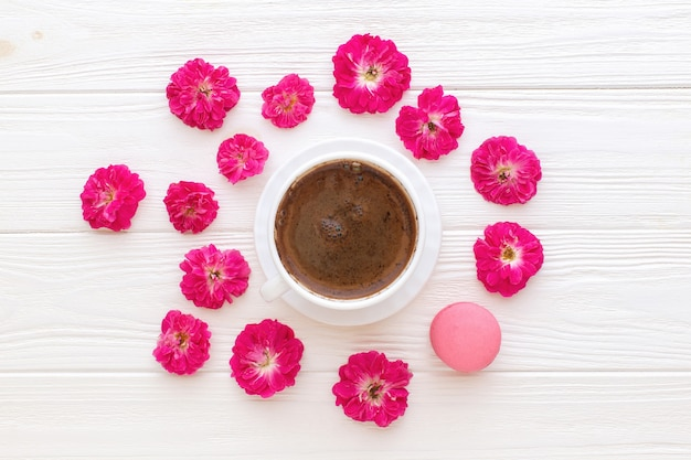 Rose tazza di caffè e amaretto rosa su fondo di legno bianco