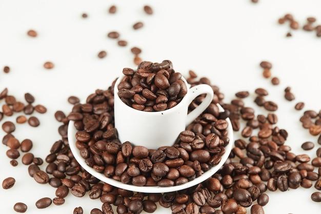 Tazza di caffè con fagioli su un piatto da vicino