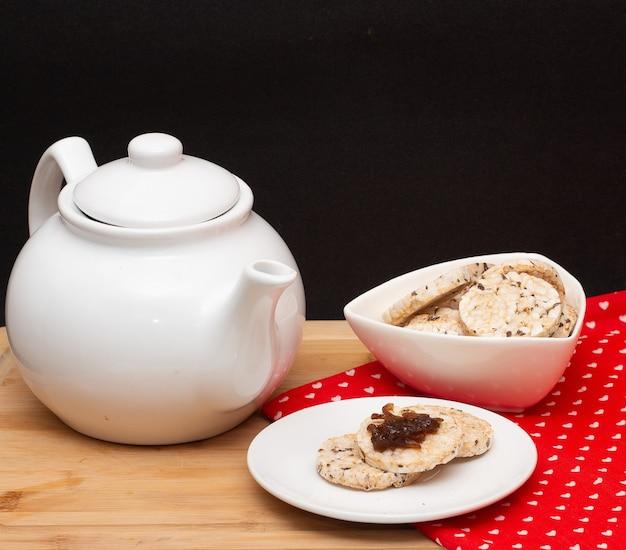 Una caffettiera circondata da una ciotola piena di biscotti vegani di riso e un piatto di biscotti di riso con gelatina sulla parte superiore