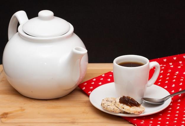Una caffettiera circondata da una tazza di caffè accanto alla gelatina di biscotti vegani di riso sulla parte superiore