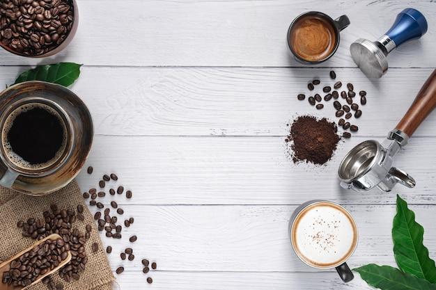 Sfondo di caffè, vista dall'alto con lo spazio della copia, caffè caldo con portafiltro da caffè, chicchi di caffè a terra sul fondo della tavola in marmo