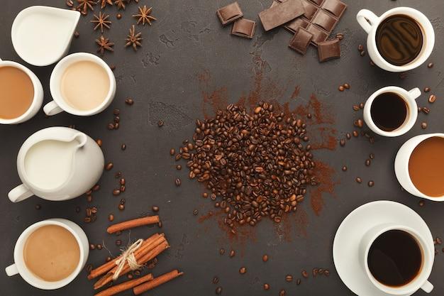 Fondo del caffè con le tazze, i fagioli, le spezie e il cioccolato assortiti sull'ardesia nera, vista superiore, spazio della copia. design orizzontale per pubblicità di bar o caffetteria