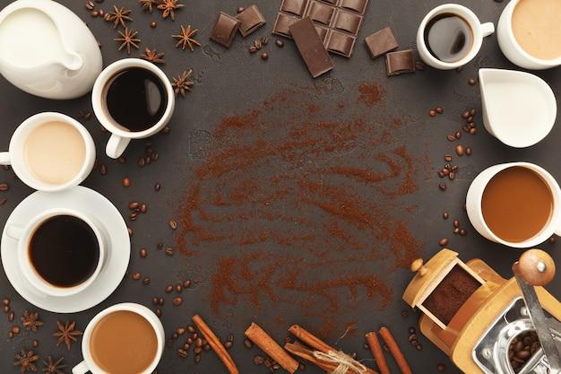 Sfondo caffè con tazze assortite, macinino vintage, fagioli, spezie e cioccolato su ardesia nera, vista dall'alto, spazio copia. design orizzontale per pubblicità di bar o caffetteria