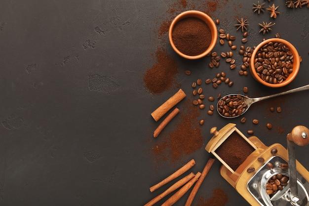 Sfondo caffè con macinino vintage, fagioli e spezie su ardesia nera, vista dall'alto, spazio copia. design orizzontale per pubblicità di bar o caffetteria