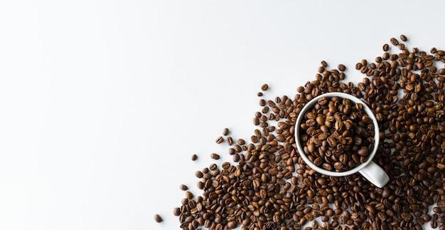 Chicco di caffè in tazza sul fondo bianco della tavola