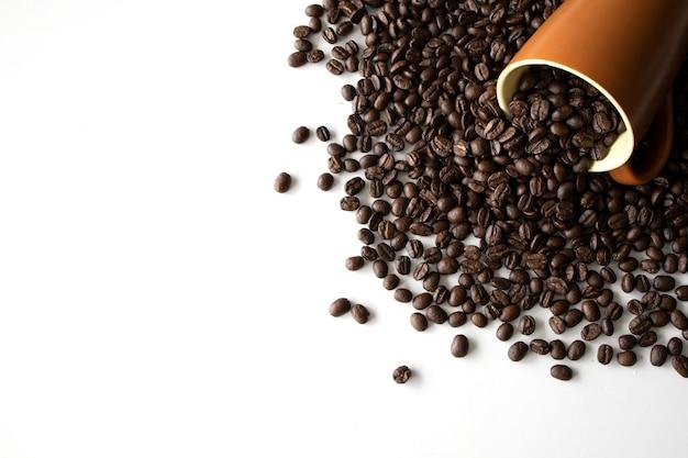 Chicco di caffè in tazza sulla tavola bianca