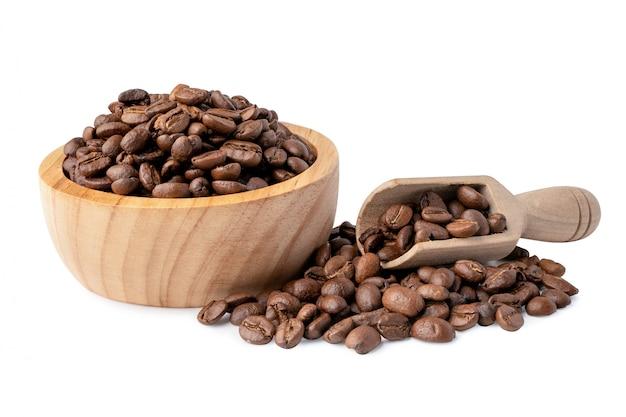 Chicco di caffè medio tostato in ciotola di legno.