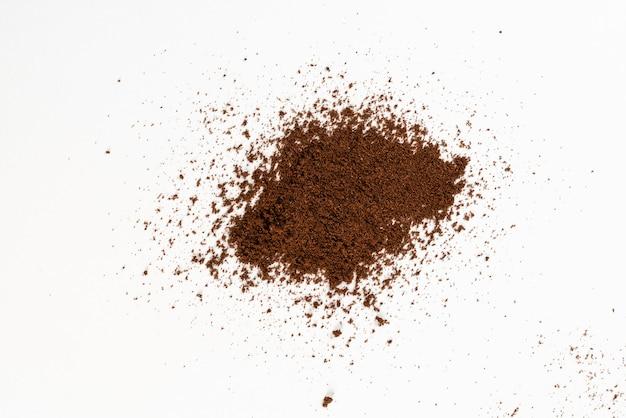 Polvere di chicco di caffè isolato su bianco