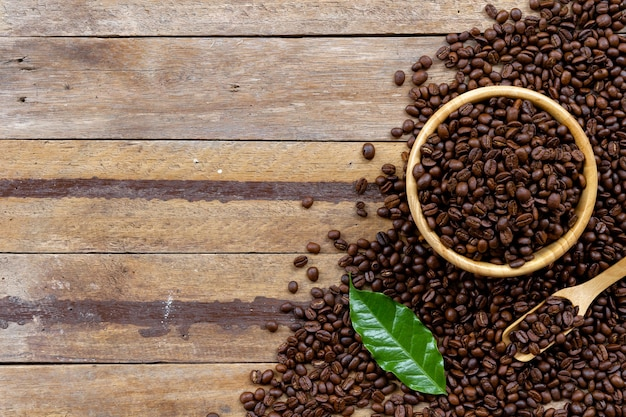 Chicco di caffè in tazza bianca sul pavimento di legno