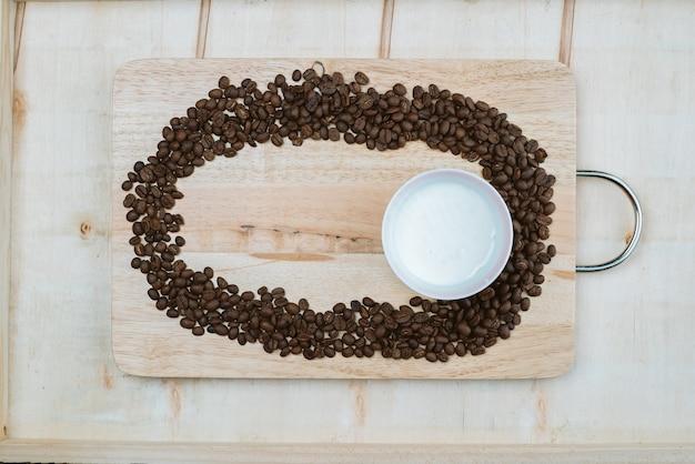 I chicchi di caffè sono fatti racchiusi intorno alle tazze di caffè che si trovano sul tabellone.
