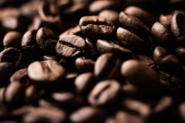 Chicchi di caffè arrostiti in background con chicchi di caffè dal sapore ricco, la migliore bevanda mattutina e una miscela di lusso