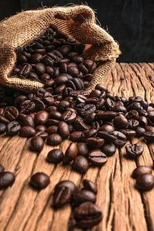 Chicchi di caffè in un sacchetto su fondo di legno vecchio