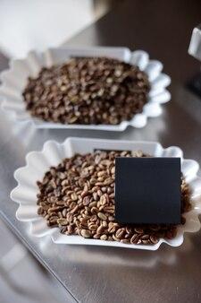 Chicchi di caffè e scatola nera su bilancia elettronica in metallo
