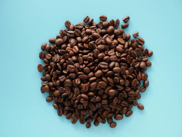 Chicchi di caffè sulla superficie blu, semi di caffè biologico