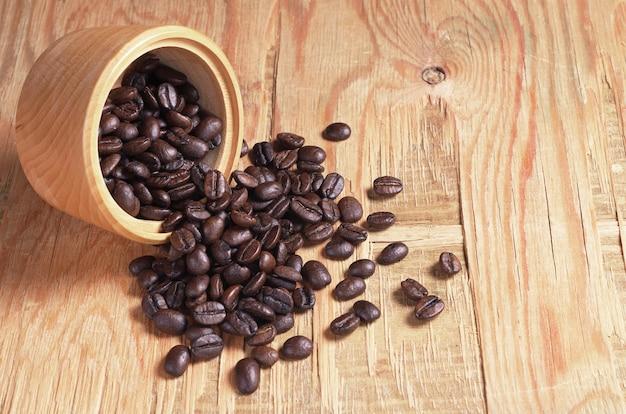 Chicchi di caffè in ciotola e vicino su vecchio fondo di legno