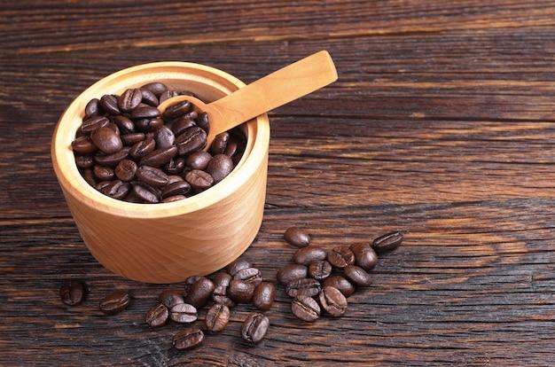 Chicchi di caffè in ciotola con cucchiaio sul tavolo di legno scuro