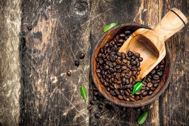 Chicchi di caffè in una ciotola su uno sfondo di legno