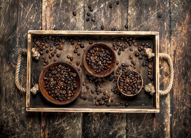 Chicchi di caffè in ciotole su un vassoio su uno sfondo di legno