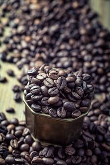 Chicchi di caffè in ciotola bronse - primi piani.