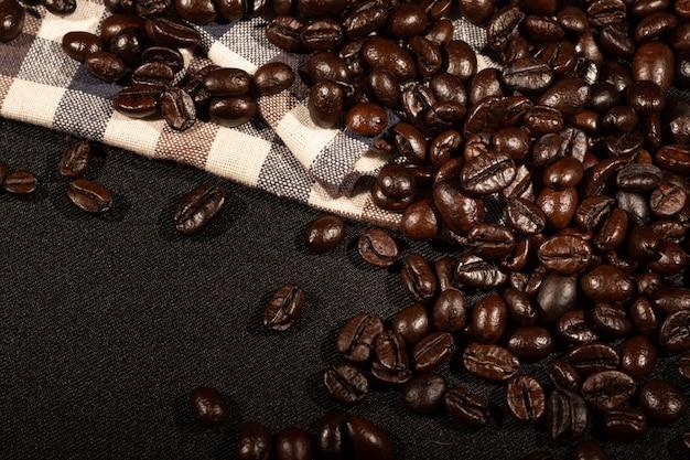 Chicchi di caffè sulla superficie marrone del tessuto di tela