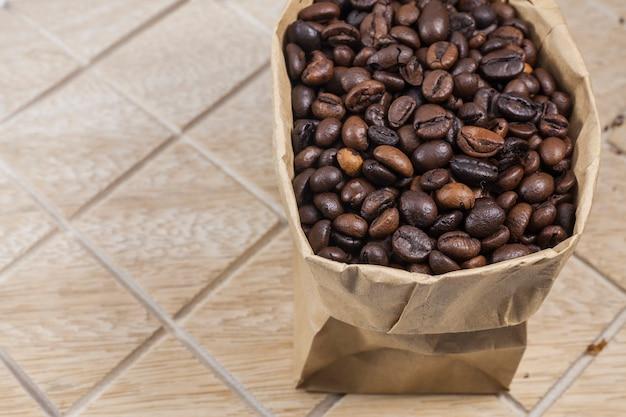 Chicchi di caffè in un sacco di carta marrone su fondo di legno.