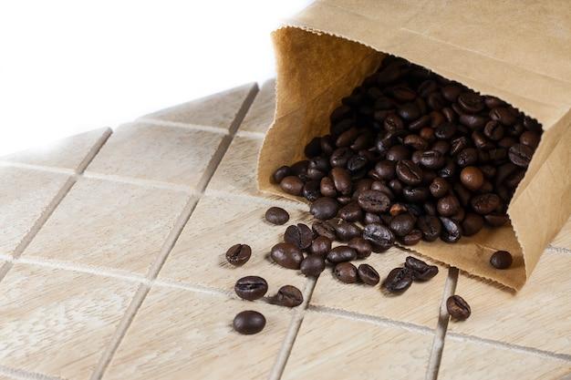 Chicchi di caffè in un sacchetto di carta marrone su una superficie di legno.