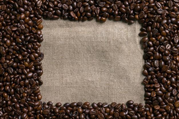 Chicchi di caffè su sfondo di tela. vista dall'alto. copia spazio. natura morta. modello. lay piatto