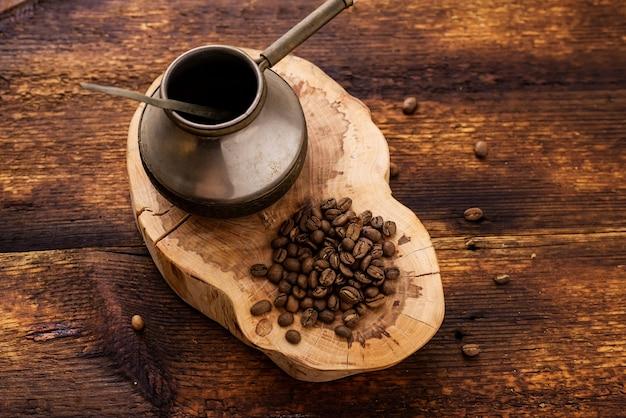 Chicchi di caffè e cezve su uno sfondo di legno.