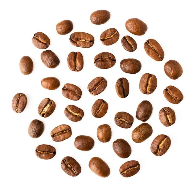 Primo piano dei chicchi di caffè su bianco