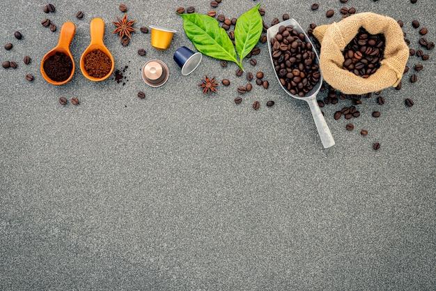 Capsula del caffè in grani e polvere del caffè sulla tavola di pietra scura.