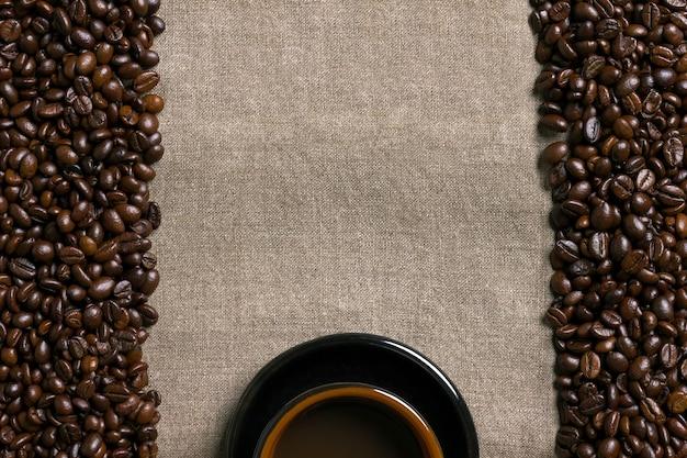 Chicchi di caffè e tazza di caffè su uno sfondo di tela. vista dall'alto. copia spazio. natura morta. modello. lay piatto