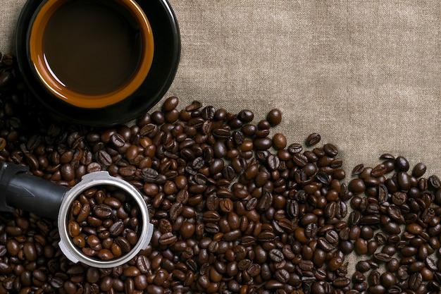 Chicchi di caffè e tazza di caffè su uno sfondo di tela