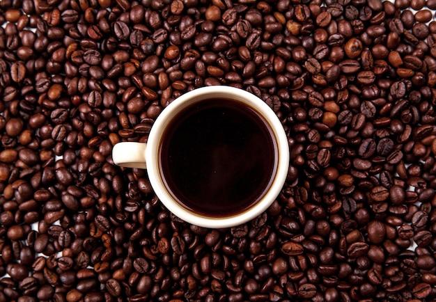 Chicchi di caffè in tazza di caffè isolato su bianco