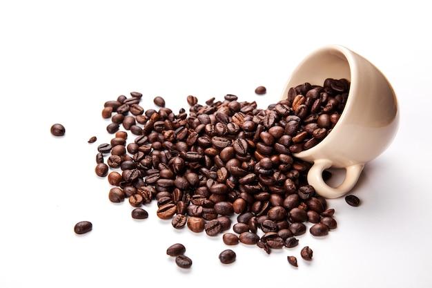 Chicchi di caffè in tazza di caffè isolati Foto Premium