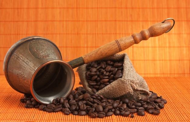 Chicchi di caffè e caffettiera in rame