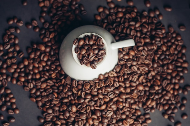 Chicchi di caffè in una tazza e primo piano grigio del fondo dei piattini bianchi. foto di alta qualità