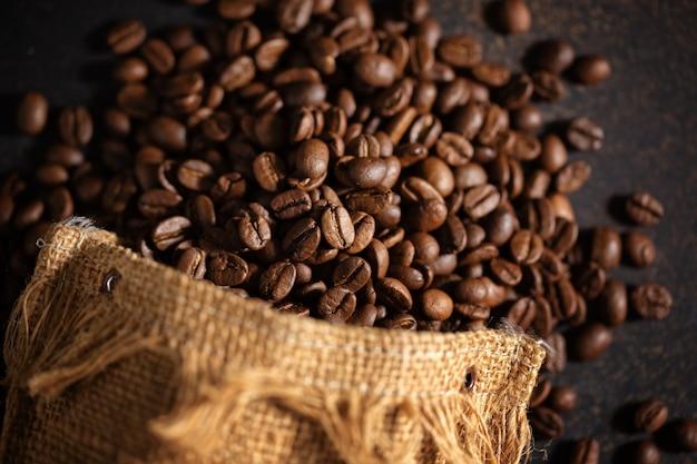 Primo piano del caffè espresso dei chicchi di caffè in borsa del sacco di iuta.