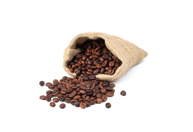 I chicchi di caffè da un sacchetto di tela vengono versati sul tavolo su uno sfondo bianco.